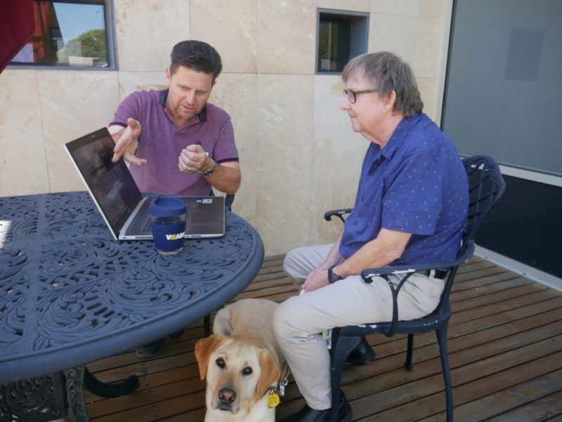 Therapist David Vosnacos sitting down with a client looking at a laptop with a Guide Dog sitting next to the client.