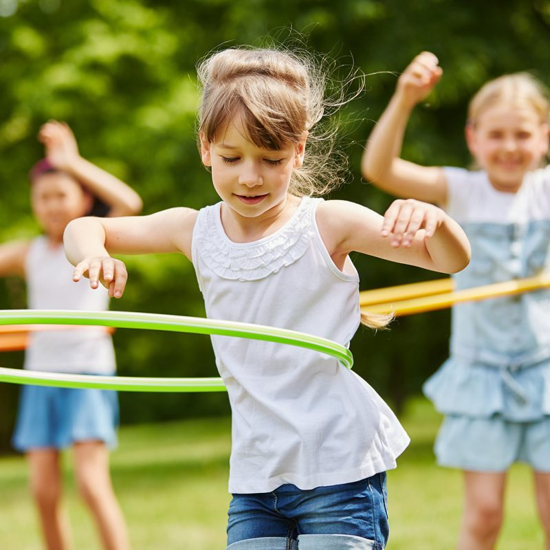 Girl hula hooping in a park with other children