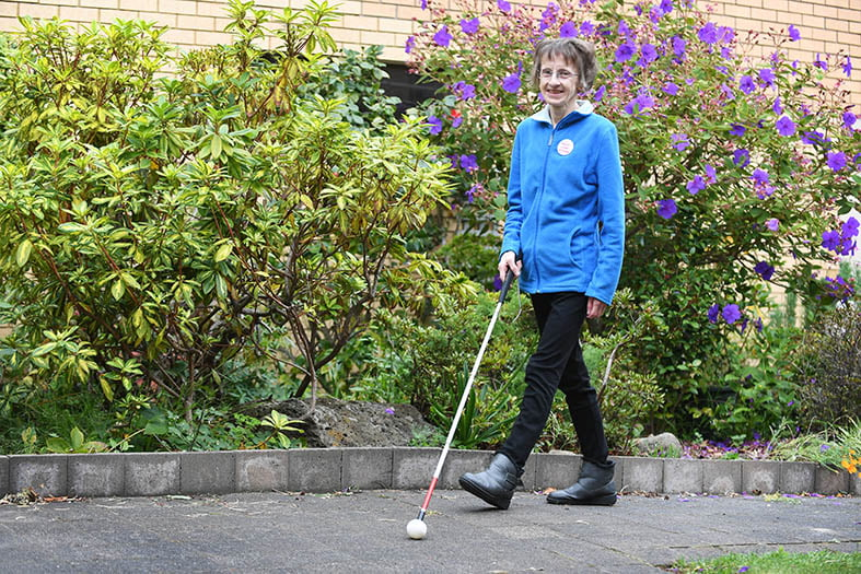 photo of a woman walking in a garden with her mobility cane