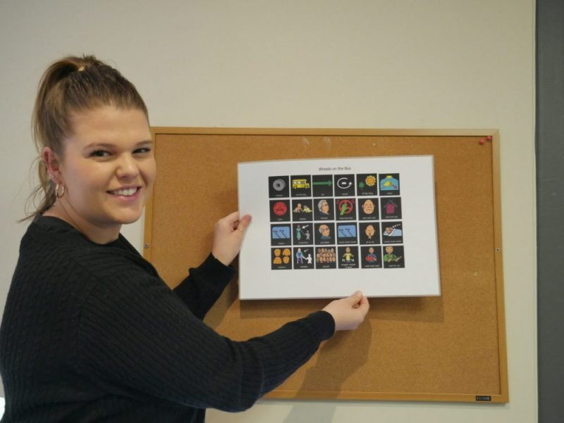 Speech pathologist Amelia Bell, pinning some speech posters with images onto a cork baord.
