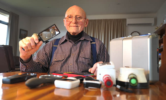 A man holding a magnifier with other items if assistive technology on the table.