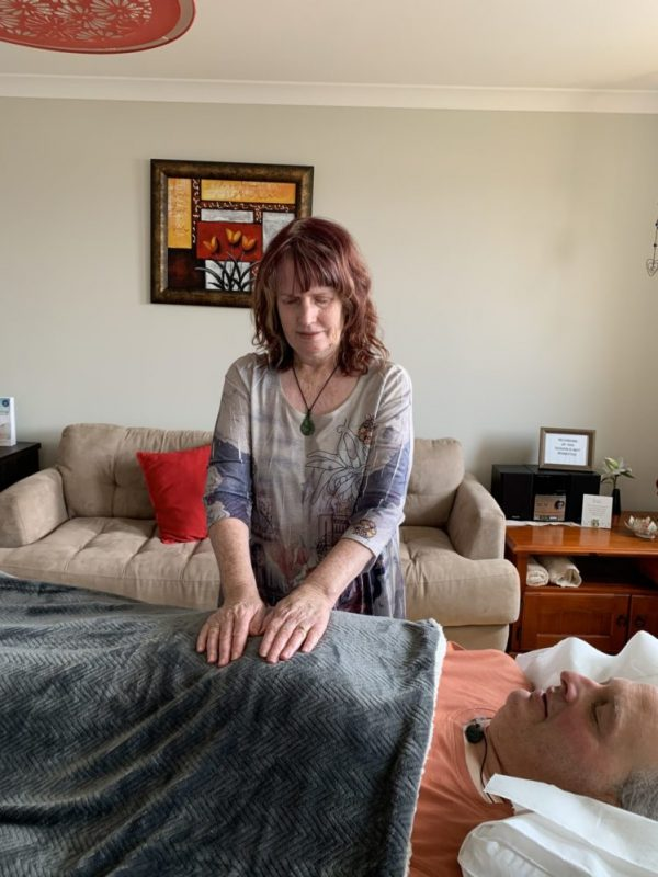 Kathryn is placing her hands on a blanket over a client as part of a hypnotherapy session