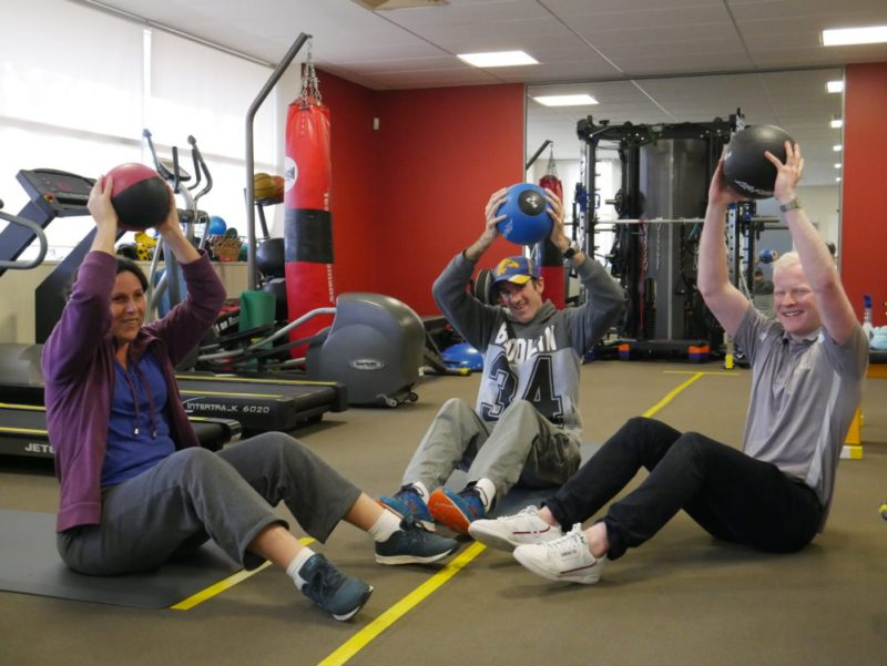 Narelle holds a weight ball, high over her head. Sitting next to her is her partner Matt also holding a weight ball along with Kane.