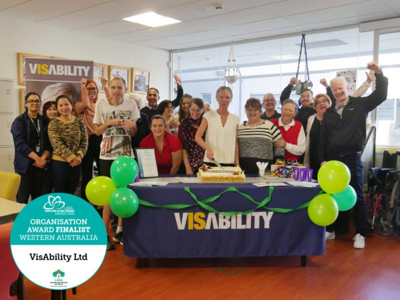 Staff and clients gathered around a table with our CEO Elizabeth Barnes cutting into a large carrot cake. VisAbility logo is pictured in the corner.