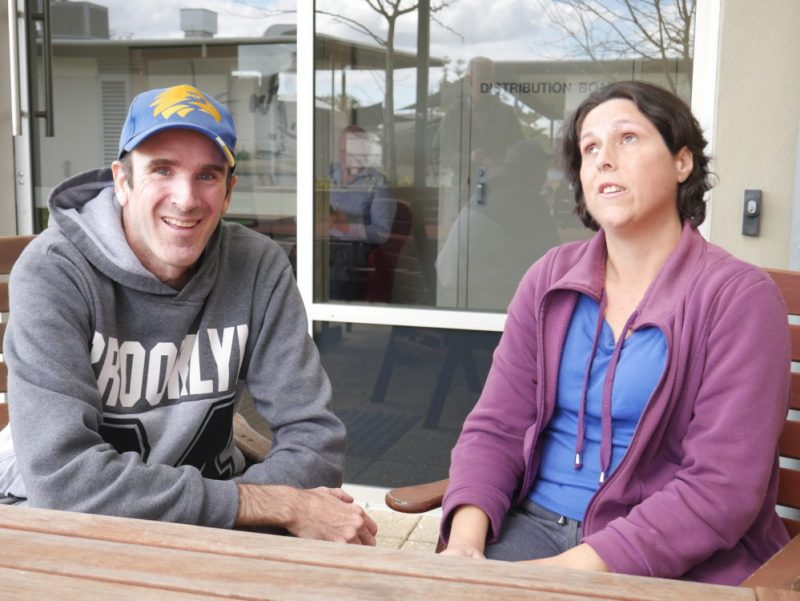 Matt and Narelle sitting next to each other in an outdoor area