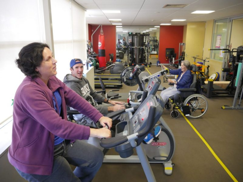Narelle and Matt in the exercise clinic on the exercise bikes with another client in the background