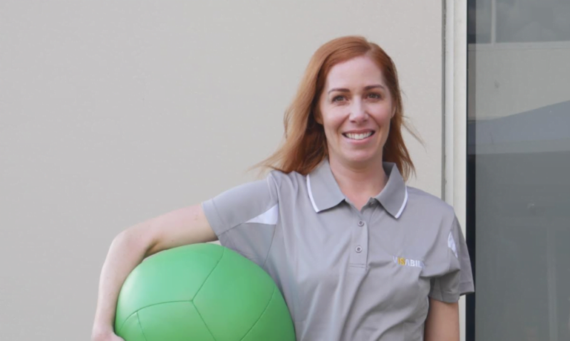 Image shows Felicity holding a large green fitness ball under her arm.