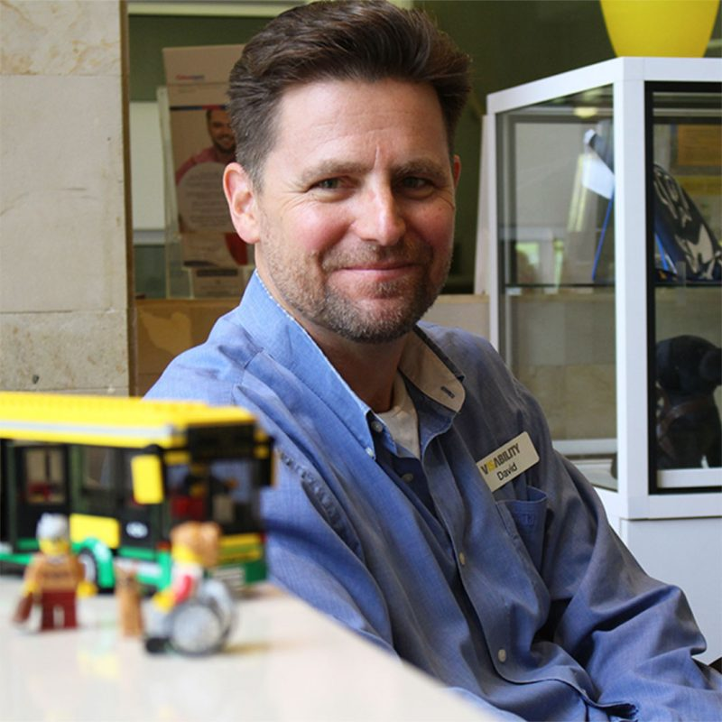David sitting in VisAbility office, next to lego construction