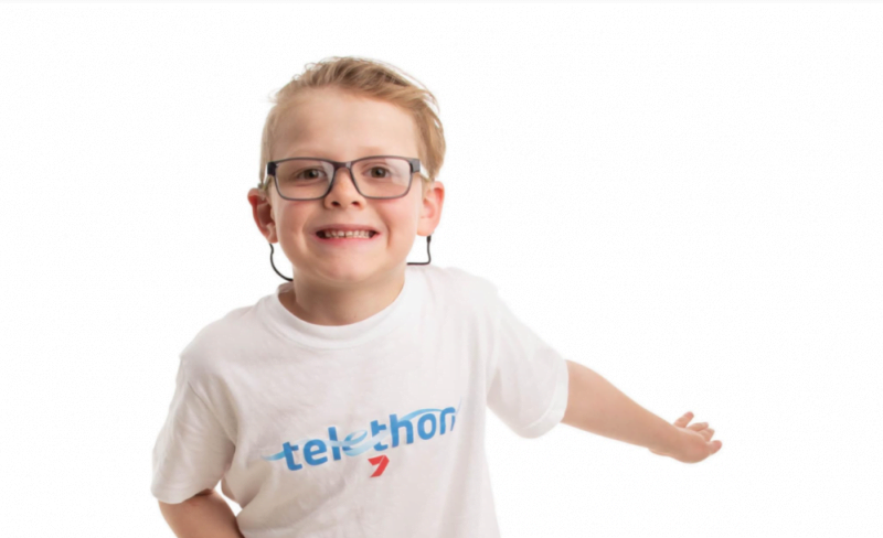 Eamon in a Telethon shirt with his arms stretched out. He's smiling and wearing glasses.