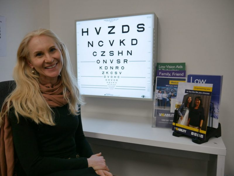 Marija faces the camera, smiling, with an eye chart and flyers in the background
