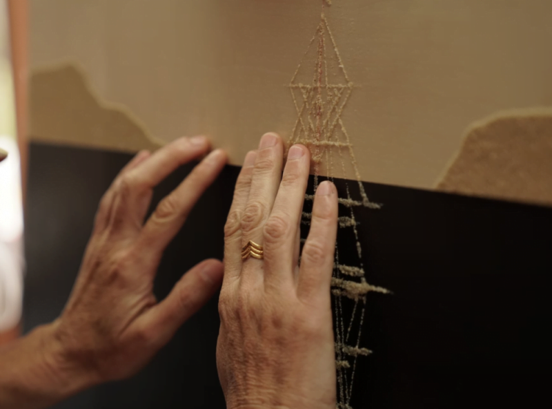 Image shows a person touching the painting and feeling the sand on the tall ship