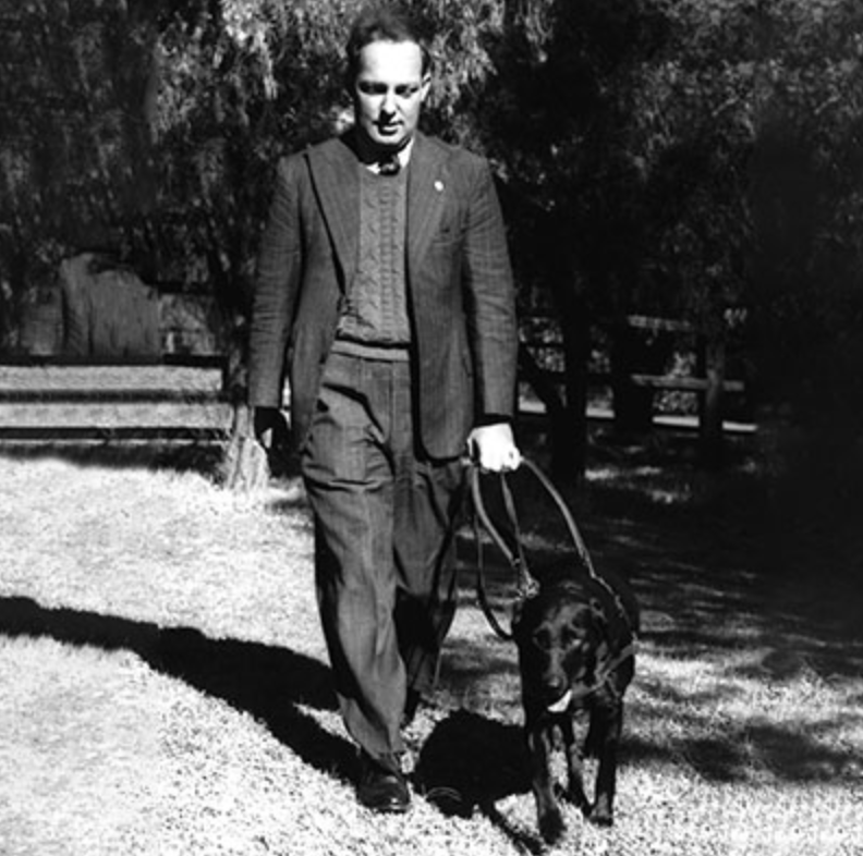 Image shows black and white photo of Dr Arnold Cook being led by his Guide Dog Dreena