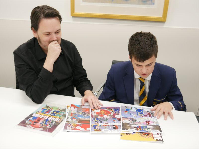 Luke Milton sits next to Thomas at a table. The two look through the comic books together.