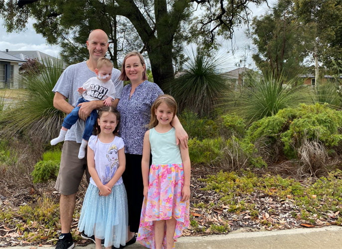 Neil stands in a garden with his wife and three children, all smiling at the camera