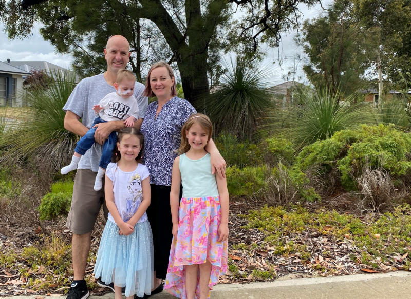 Neil stands with his wife and three young cildren against a background of shrubbery and trees