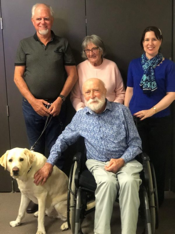 Four people in a group. One person is in a wheel chair. A man standing up has a Guide Dog.