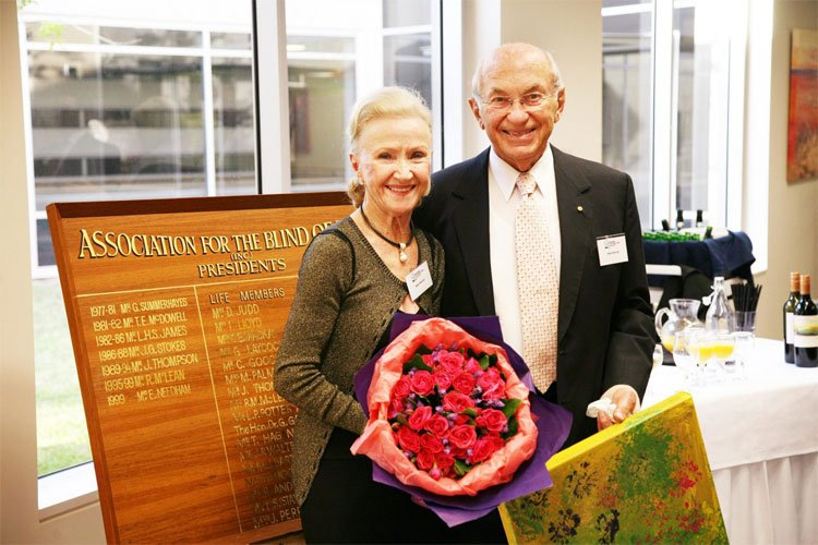 Jean and Stan Perron holding flowers and a gift in front of the Association for the Blind Life Members board
