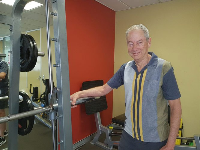 John in his workout gear next to some exercise equipment