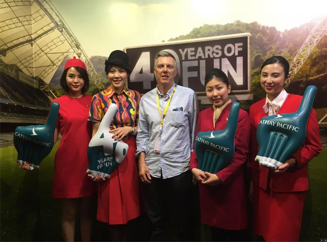 Image of John Nolan surrounded by Cathay Pacific airways staff in a sports stadium at a key sporting event