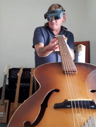Les, wearing magnifying glasses, looks over a guitar