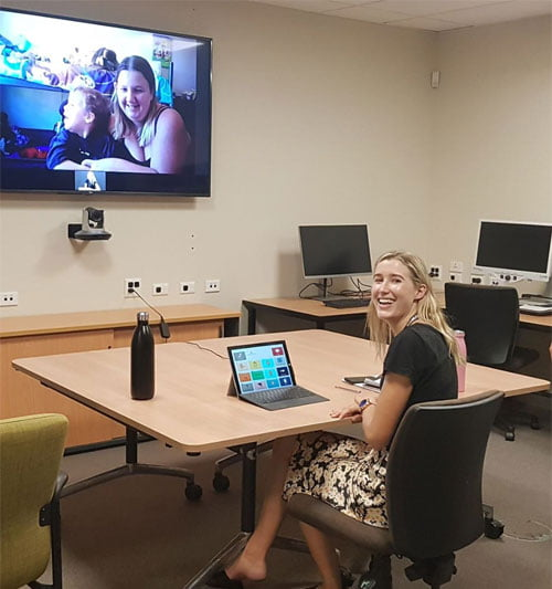 """Speech Therapist Monique sits in a large room with a laptop in front of her, client in bigger screen directly in front of her."""" width=""""299"""" height=""""319"""" /> Speech Therapist Monique Ziegelaar conducting an online therapy session"""