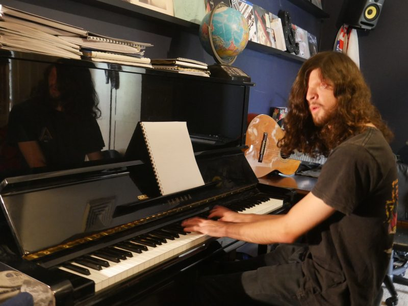 Richard playing his piano in his bedroom