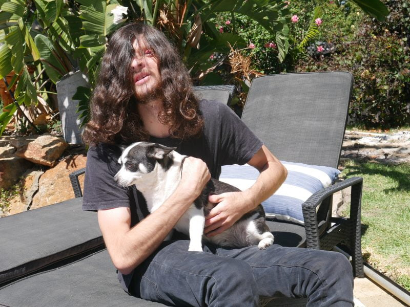 Richard sits on a garden chair and is holding his dog