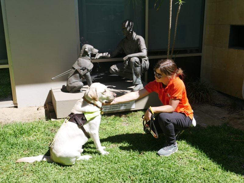 Guide Dog Instructor Emily poses with blonde Labrador alongside Dr Arnold Cook statue