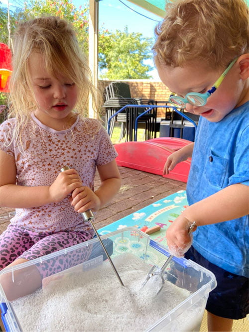Two children, a boy and a girl play with a whisk in a tub of sand as part of an interactive VisAbility playgroup session.