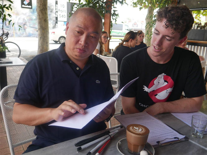 Manny, sits next to Cormac reading the Braille menu