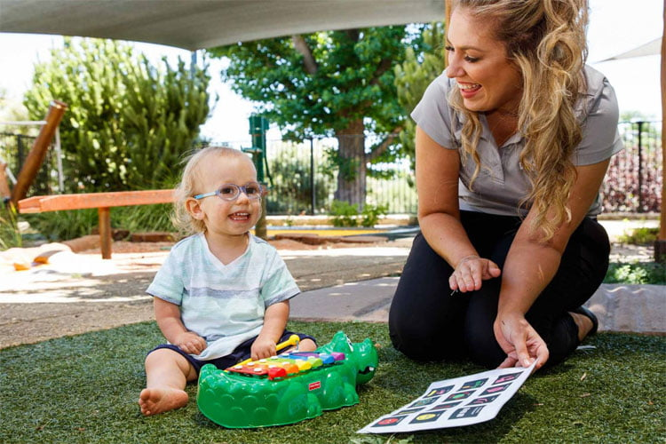 A young boy plays on the grass with a xylophone, and VisAbility team member Caris holds an aided language display