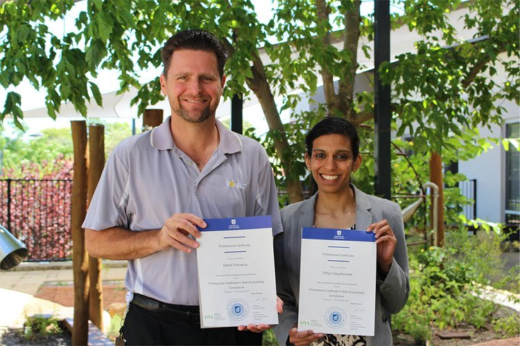 David and Vithya, standing in a VisAbility garden holding their certificates