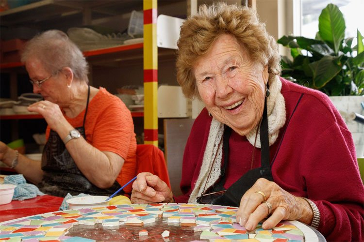 A lady in a red jumper is smiling as she works on a mosaic
