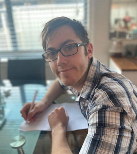 Darren sits at a table, with pen and paper in hand. He is smiling at the camera