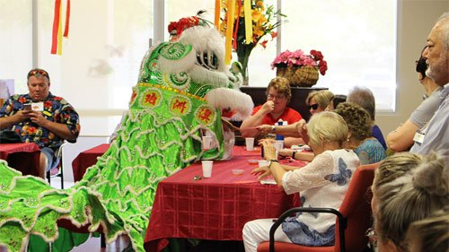 The lion dance as clients reach out with red packets to give the bright green dragon with white fur
