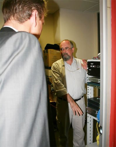 Prof Murray is standing next to an IT system pointing to it explaining how it operates to a visiting guest