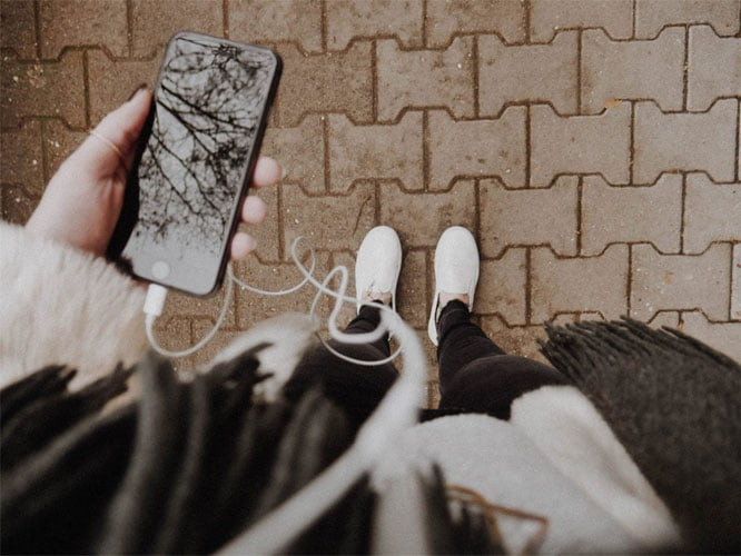 Image of a person holding a phone with headphones