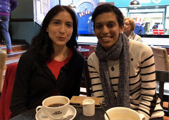 Dr Mariana Lopez and Vithya Vijayakumare sitting in a coffee shop.