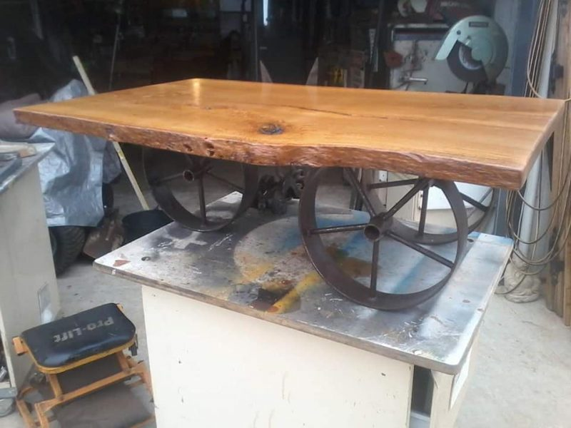 A wooden table made from a slab of wood with wheels underneath