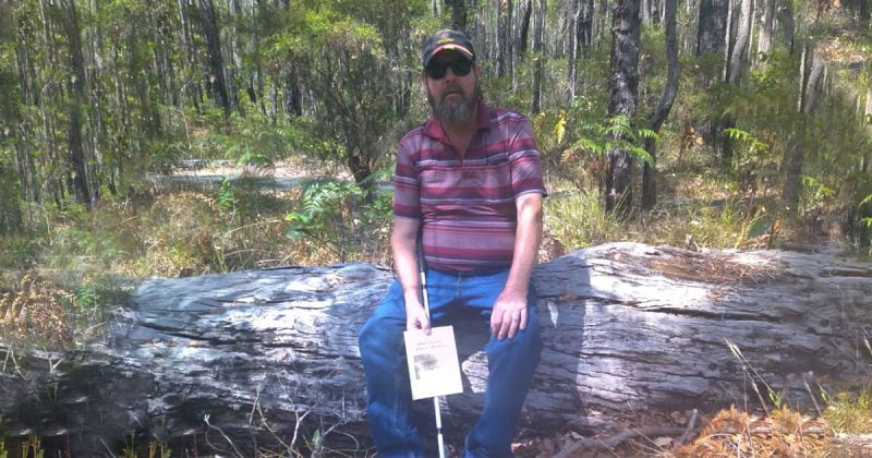 Phil sits on a log in a forest. He is holding his white cane
