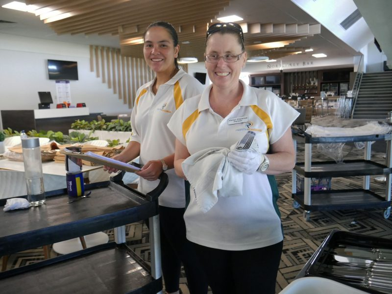 Bridie stands next to a colleague in front of a tray polishing cutlery