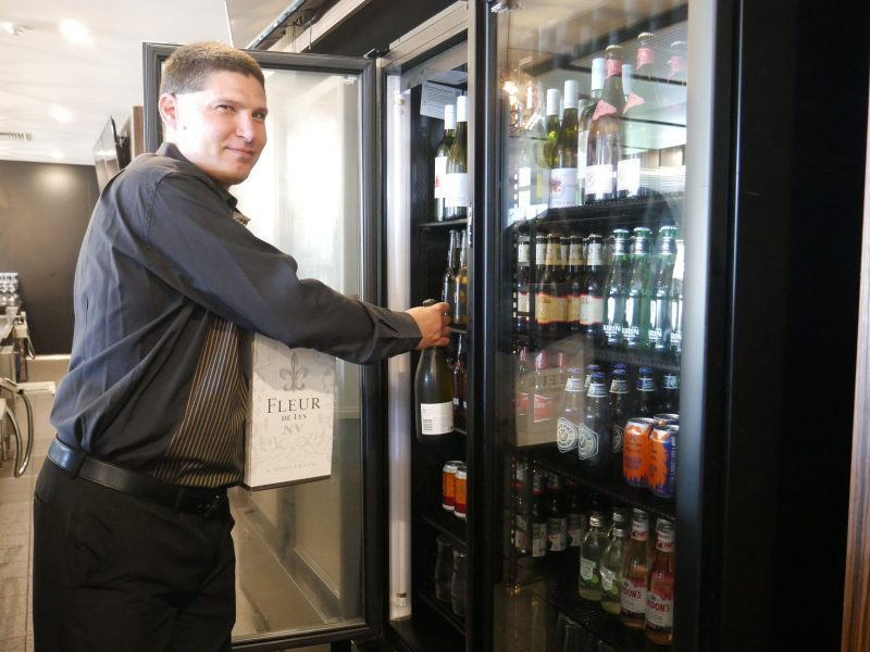 Danyel is placing cool bottles into a tall commercial fridge