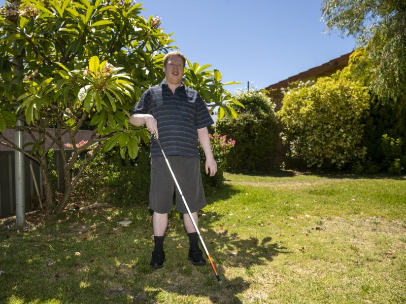 Graham standing in his garden with his white cane