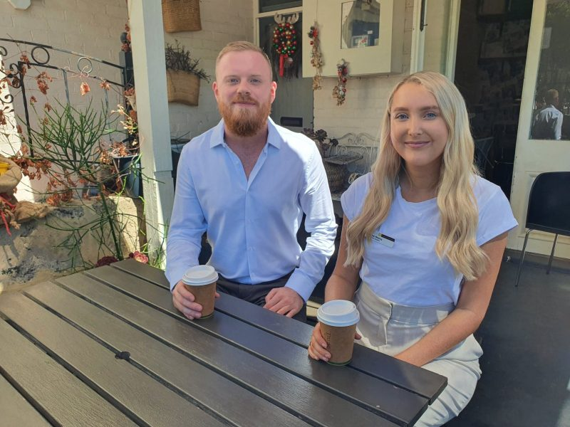 Beau and Emalee sit around a wooden table in outdoor area of cafe