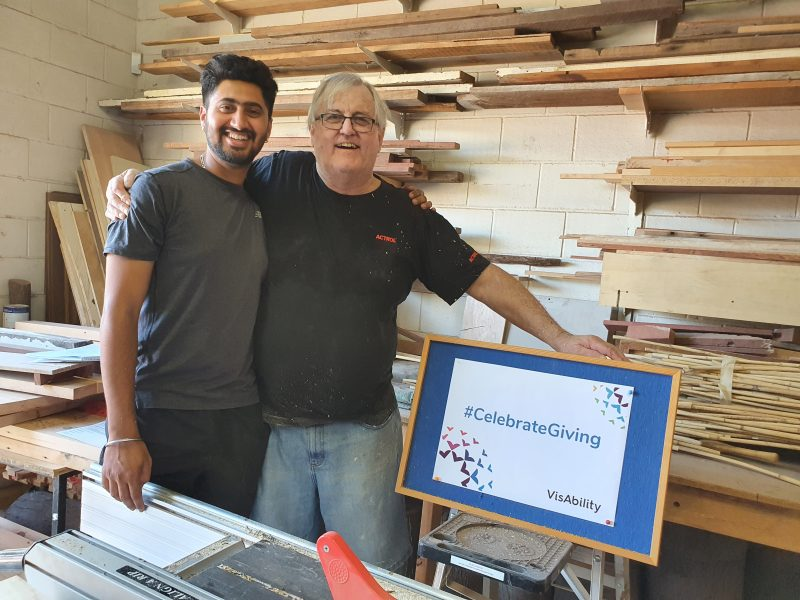 Rohit and Alan stand next to each other in the woodworking shed