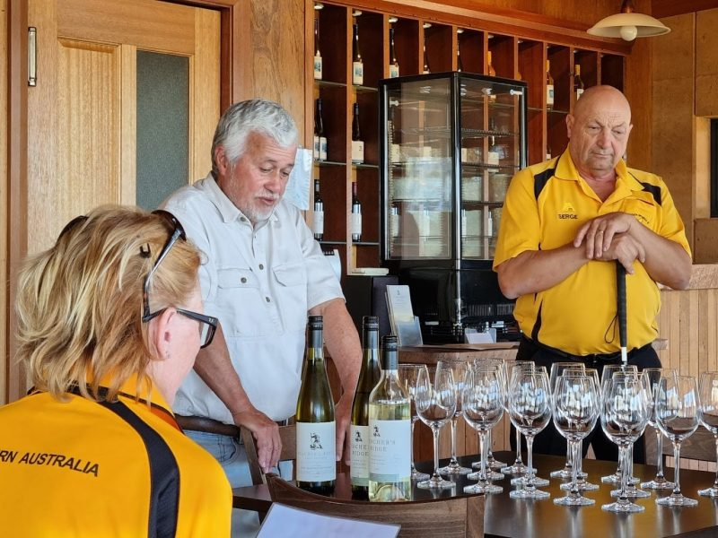 Serge stands next to a vineyard owner who's giving a talk about wine. There are glasses on the table in front of him.
