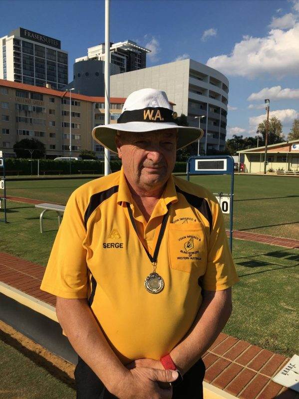 Serge standsin front of a bowling green in his bowls uniform with gold medal around his neck