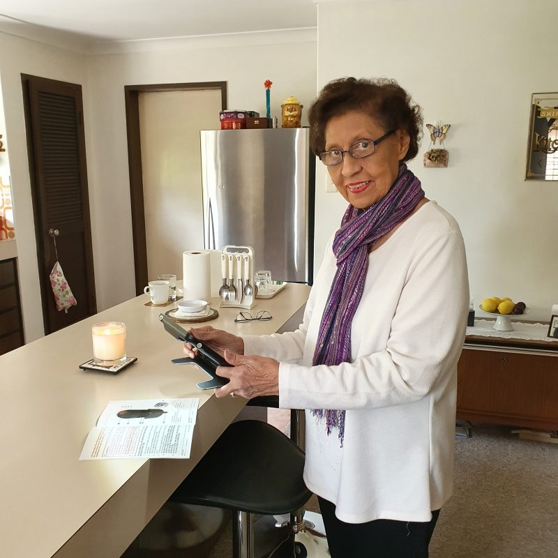 Shirley standing in kitchen holding a video magnifier