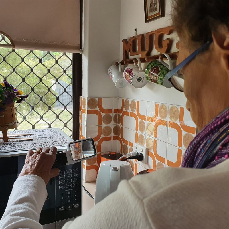 Shirley holding a magnifier to read numbers on her microwave