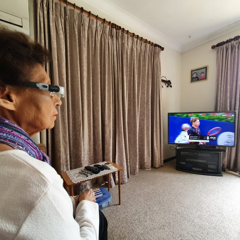 Shirley looks at a tv screen wearing the magnifying glasses